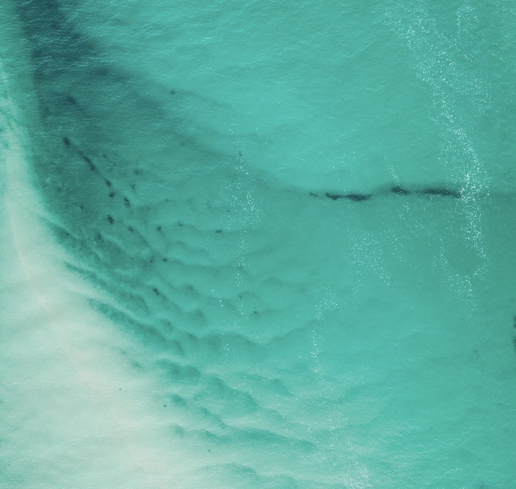 An aerial view of a turquoise sea and patterns of waves in the sand