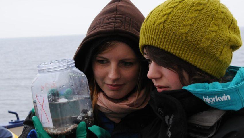 Zwei Schülerinnen stehen bei einer Exkursion am Meer und sehen sich eine wissenschaftliche Probe an