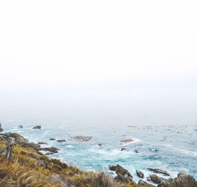 Eine Steile Küste mit Wellen die sich an Felsen brechen, das Meer liegt in weißem Dunst