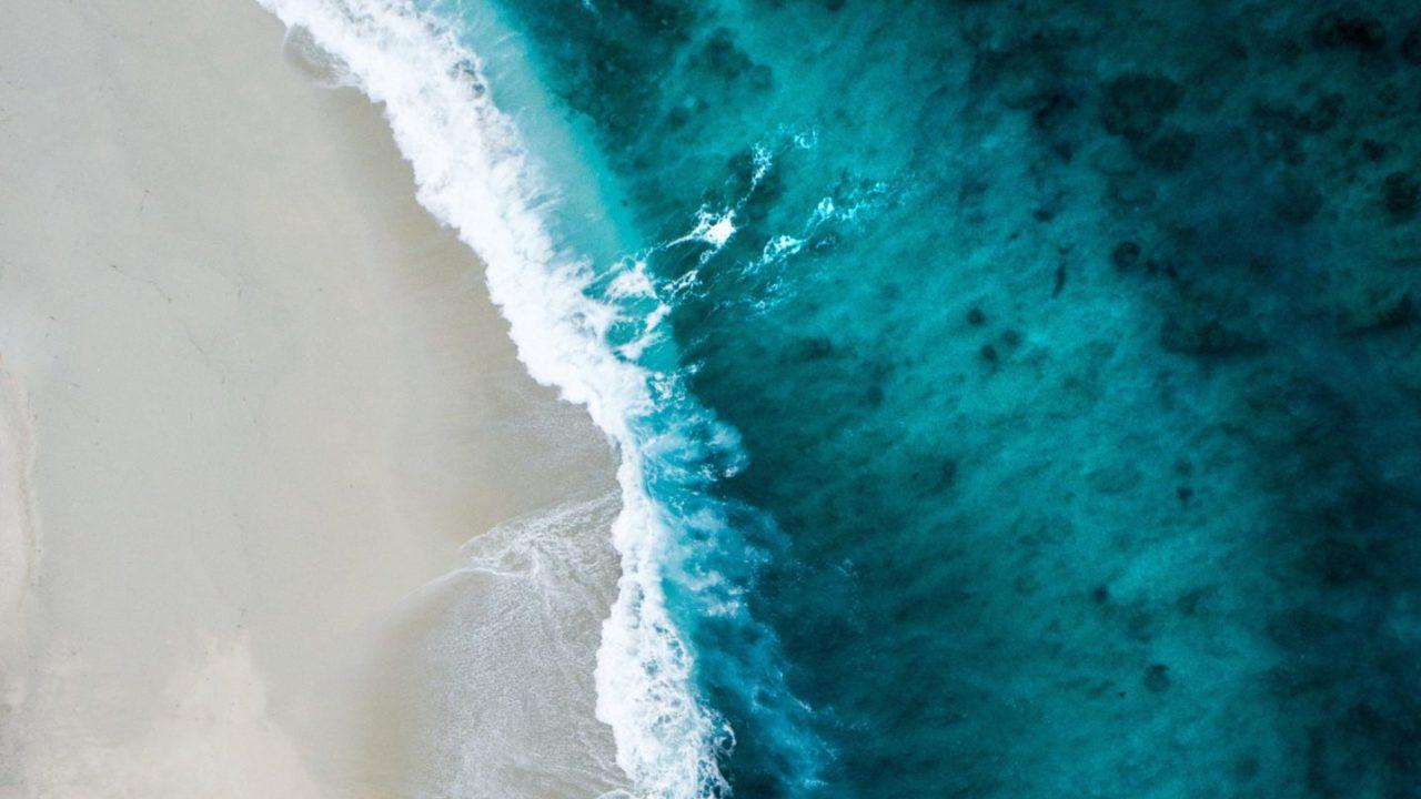 Große Wellen mit Gischt rollen auf den Strand