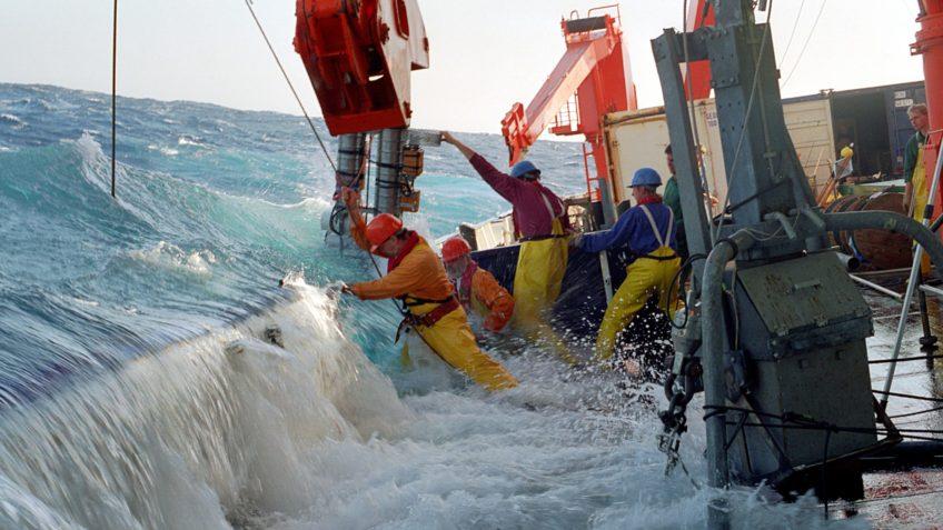 Eine große Welle schwappt über die Bordwand eines Forschungsschiffs