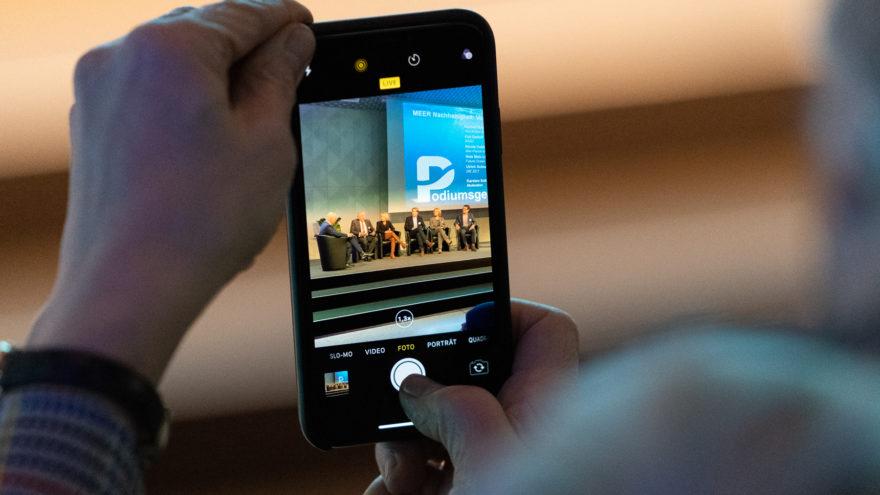 Aufnahme eines Smartphones mit einer Aufnahme der Podiumsdiskussion auf der Bühne bei der Auftaktveranstaltung der DAM
