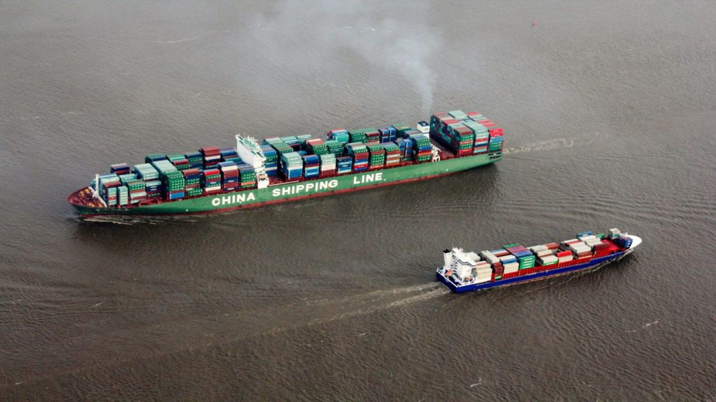 Two ships loaded with containers travel on the sea