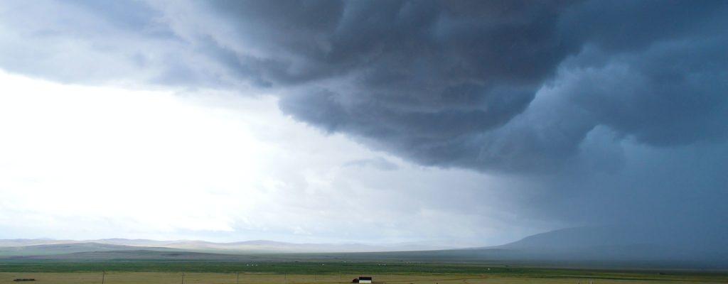 Sturm Wolken über Wiesen und Bergen